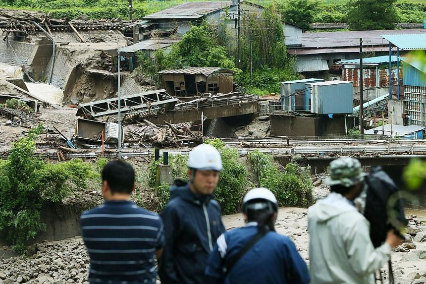 A TV crew works near the Nashizawa river at Nagiso town in Nagano prefecture, central Japan on July 10, 2014 following a mudslide. -- PHOTO: AFP
