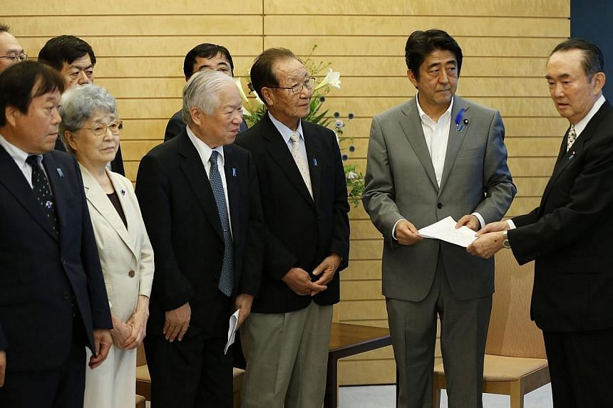 """Japan's Prime Minister Shinzo Abe (2nd right) receives a petition from members of North Korean abduction issue groups at Abe's official residence in Tokyo on July 4, 2014.Japan on Thursday denied as """"sheer misreporting"""" a front-page newspaper s"""