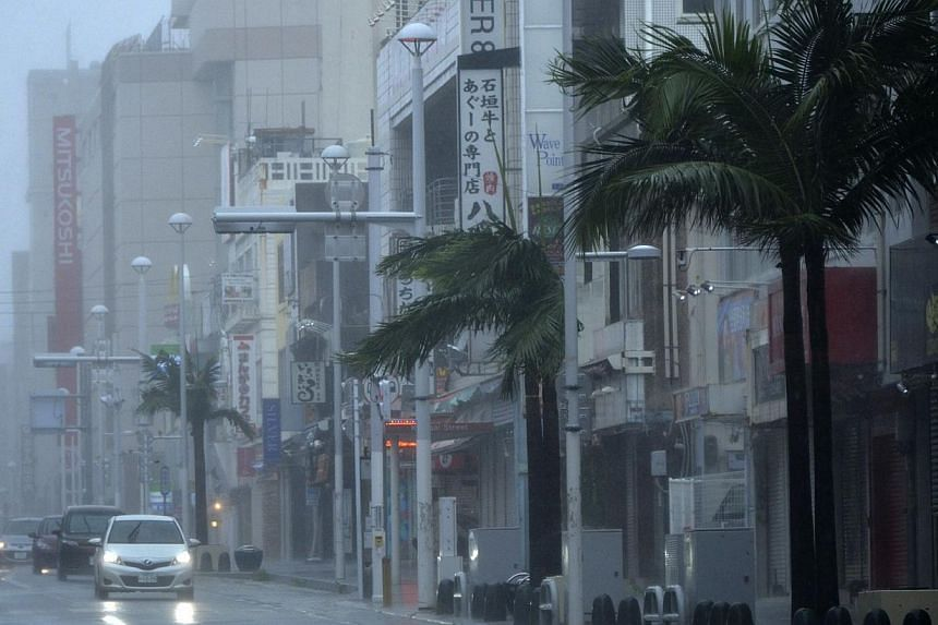 Roadside trees are blasted by strong winds along relatively empty streets in Naha on Japan's southern island of Okinawa as Typhoon Neoguri hit the area on July 8, 2014.Typhoon Neoguri slammed into Japan's southern main island early Thursday aft