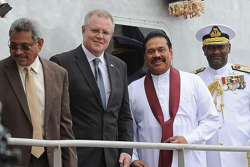 Sri Lankan President Mahinda Rajapakse (2nd right) and Australia's immigration minister Scott Morrison (2nd left) pose for photographers in Colombo on July 9, 2014 during a ceremony commissioning two Australian-gifted naval patrol boats that will be