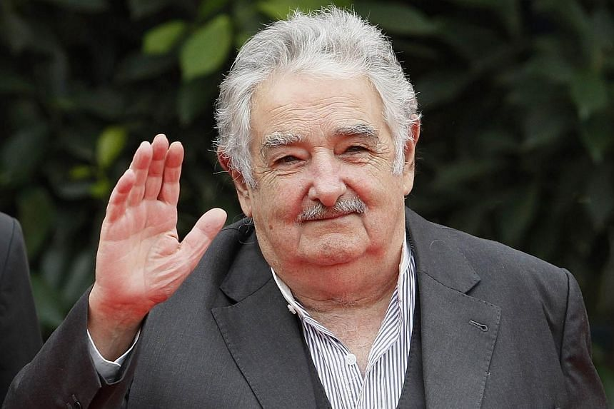 Uruguay's President Jose Mujica waves to the media during the ceremonial greeting of heads of states at the G77+ China Summit in Santa Cruz de la Sierra on June 15, 2014.Uruguay President Jose Mujica told AFP on Wednesday that sales of marijuan