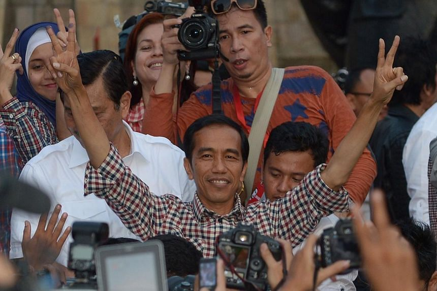 Indonesian presidential candidate Joko Widodo (centre) gestures with his running mate Jusuf Kalla after delivering a speech at Tugu Proklamasi square in Jakarta on July 9, 2014. -- PHOTO: AFP