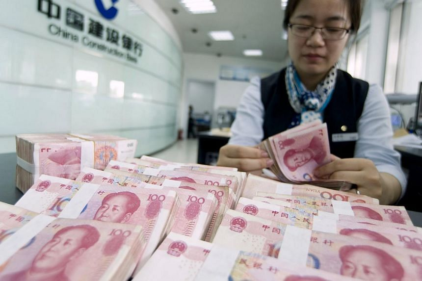 A clerk counts Chinese 100 yuan banknotes at a branch of China Construction Bank in Hai'an, Jiangsu province on June 10, 2014. -- PHOTO: REUTERS