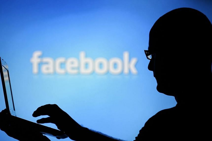 A man is silhouetted against a video screen with an Facebook logo on Aug 14, 2013.Facebook is coming under scrutiny in Myanmar as an unwitting platform for a rising tide of hate speech following a new wave of Buddhist-Muslim bloodshed in the fo