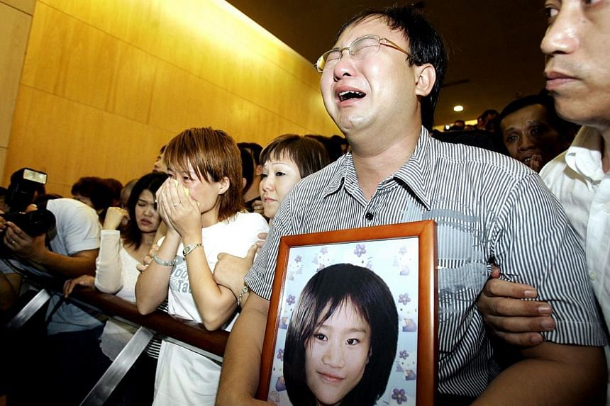 Huang Na's parents had to be supported and held back at the Mandai Crematorium as they watched their daughter's coffin roll into the furnace.-- PHOTO: ST FILE