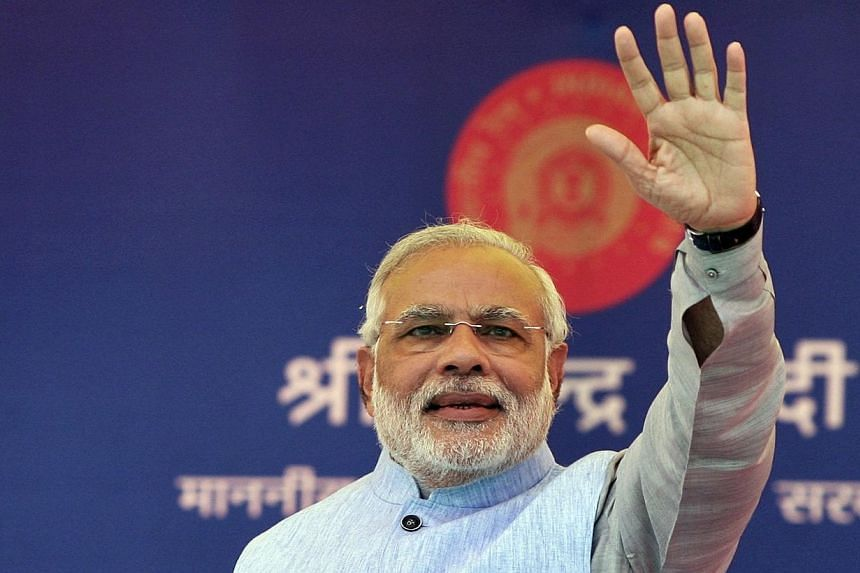 Indian Prime Minister Narendra Modi waves to a crowd at a gathering after inaugurating a train on a new stretch of railway to the town of Katra, north-west of Jammu on July 4, 2014. Mr Modi on Friday, July 11, 2014, accepted an invite to meet US Pres