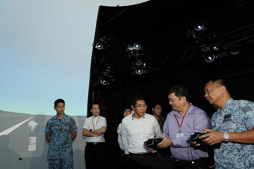 Chairman of the Government Parliamentary Committee for Defence and Foreign Affairs, Mr Sitoh Yih Pin (second from right), accompanied by Minister of State for Defence, Dr Mohamad Maliki Osman (third from right), trying out the Unmanned Aerial Vehicle