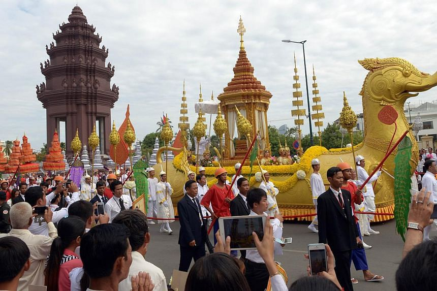 Cambodian Royal convoy carry urns past the Independent monument during a procession of the remains of the late former King Norodom Sihanouk in Phnom Penh on July 11, 2014. -- PHOTO: AFP