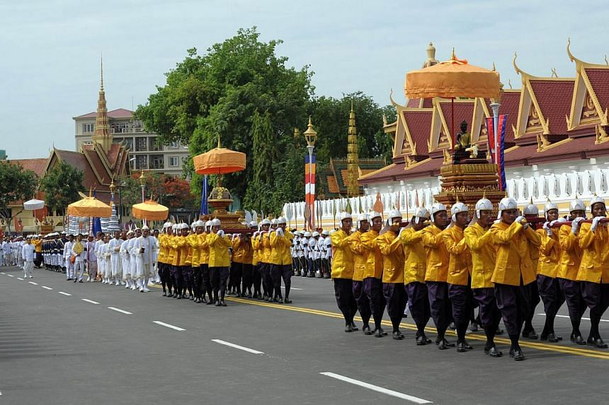 Cambodian royal officials carry urns during a procession of the remains of the late former king Norodom Sihanouk in front of the Royal Palace in Phnom Penh on July 11, 2014. -- PHOTO: AFP