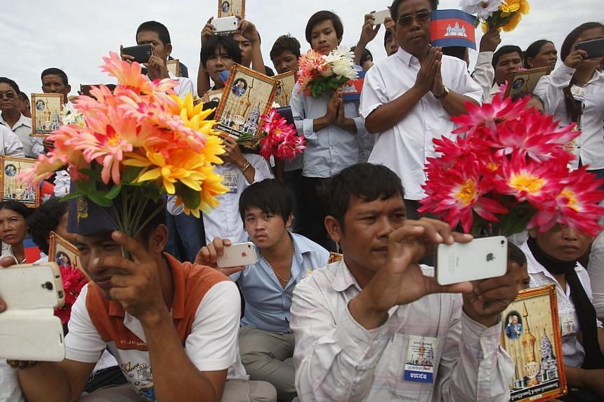 People watch a royal procession transporting the remains of late Cambodian King Norodom Sihanouk marches en route to the Royal Palace during a ceremony in Phnom Penh on July 11, 2014. -- PHOTO: REUTERS
