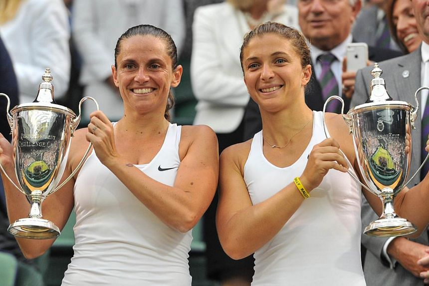 Newly-crowned Wimbledon women's doubles champions Sara Errani (right) and Roberta Vinci have become the first players to qualify for the BNP Paribas WTA Finals Singapore tournament from Oct 17-26. -- PHOTO: AFP