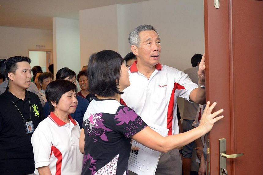 Prime Minister Lee Hsien Loong (right) being briefed by Ms Wendy Tan (second, right), Director of ONG&ONG Pte Ltd on Home Improvement Programme features at Teck Ghee on July 12, 2014. Mr Lee explained the benefits of an upgrading programme to som