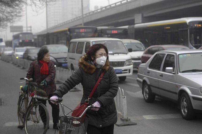 A woman (centre) wearing a mask stands besides her bicycle as vehicles stop at a traffic junction on a busy street amid thick haze in Beijing on Feb 25, 2014. China's capital city, Beijing, will enforce the use of cleaner low-sulphur coal from A