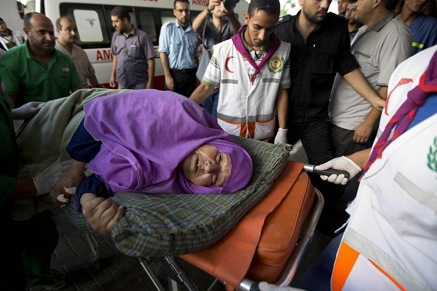 A Palestinian woman is brought into an hospital on a stretcher after she was injured in an Israeli air strike on July 11, 2014 in Gaza City. -- PHOTO: AFP