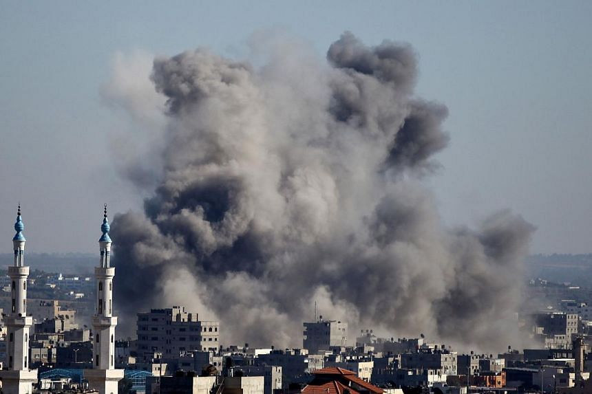 Smoke billows from buildings following an Israeli air strike in Gaza City on July 11, 2014.Separate Israeli air strikes early on Saturday killed three people in Jebaliya, in the northern Gaza Strip, and two further south in Deir el Balah, emerg