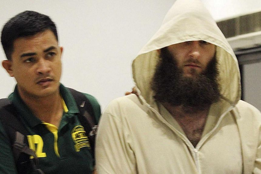 Robert Cerantonio (R), an Australian national and a Muslim convert, is escorted by police intelligence upon arrival at the domestic airport in Manila on July 11, 2014. -- PHOTO: REUTERS