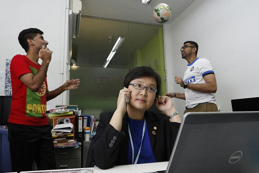 Ms Juliet Soh (centre), an IT marketer, shares office space with D2D Sports' Mr Alvinder Singh (left) and Mr Rasvinder Singh (right) at The Office. -- PHOTO: DESMOND LUI FOR THE SUNDAY TIMES