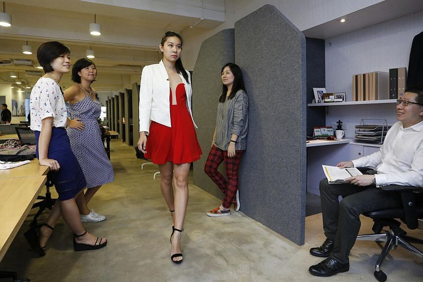 A model in a red dress practises her walk in front of Fashvacation managers (from left) Chang Zi Ying, Natalie Png and Audrey Ti at The Co. Sharing their office space is Mr Peter Ong, managing partner of a business advisory firm. -- PHOTO: DESMOND LU