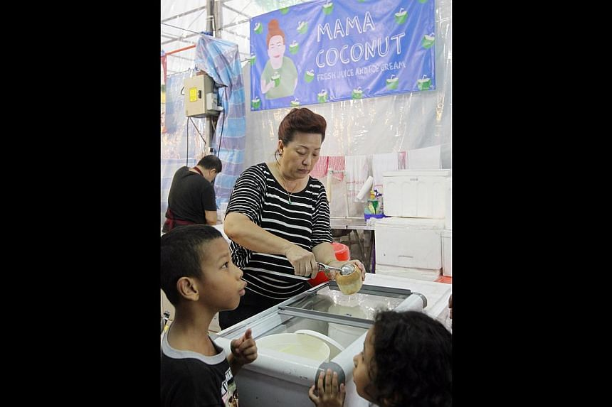 The Hari Raya bazaar in Geylang Serai offers more than just festival wares. Stalls such as Chubby Churrosselling the Spanish snack, Mama Coconut (above) selling ice cream and drinks, and Soulhunterz Haunted House are doing good business too. -- ST PH