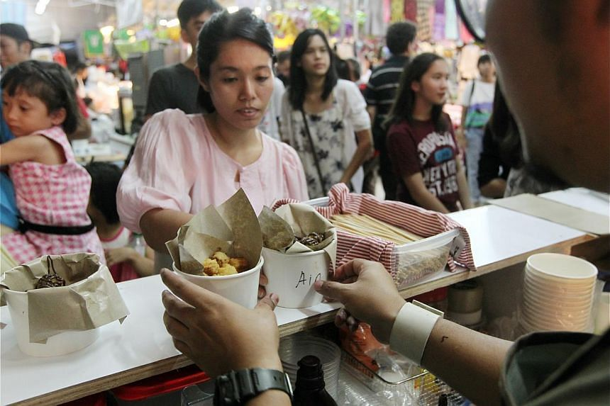 The Hari Raya bazaar in Geylang Serai offers more than just festival wares. Stalls such as Chubby Churros (above) selling the Spanish snack, Mama Coconut selling ice cream and drinks, and Soulhunterz Haunted House are doing good business too. -- ST P