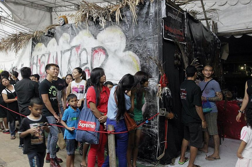 The Hari Raya bazaar in Geylang Serai offers more than just festival wares. Stalls such as Chubby Churros selling the Spanish snack, Mama Coconut selling ice cream and drinks, and Soulhunterz Haunted House (above) are doing good business too. -- ST P