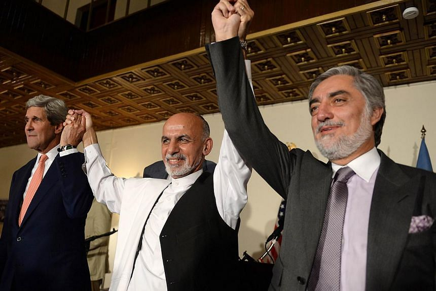 (From left) US Secretary of State John Kerry, Afghan presidential candidates Ashraf Ghani and Abdullah Abdullah hold hands during a joint press conference in Kabul on July 12, 2014.-- PHOTO: AFP