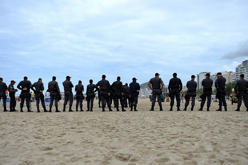 Military police officers stand guard at the Copacabana beach in Rio de Janeiro on July 12, 2014, on the eve of the 2014 FIFA World Cup final between Germany and Argentina at the Maracana Stadium. -- PHOTO: AFP