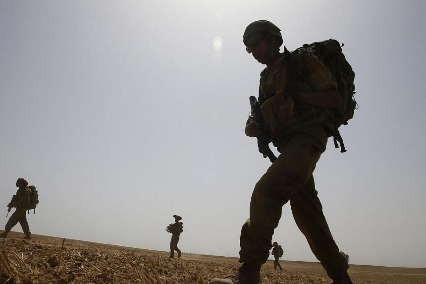 Israeli soldiers from the Nahal Infantry Brigade walk across a field near central Gaza Strip on July 12, 2014.Israeli navy commandos clashed with Hamas gunmen during a raid on the coast of the Gaza Strip on Sunday, the first such gunfight of a