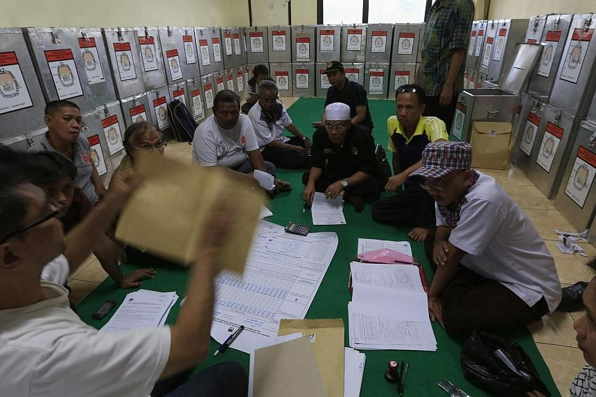 Election commission official Dedi Saidi (left) checks a document stating the number of votes collected in ballot boxes, at Bendungan Hilir in Jakarta, on July 10, 2014. Indonesia's young democracy faces its biggest challenge since emerging from