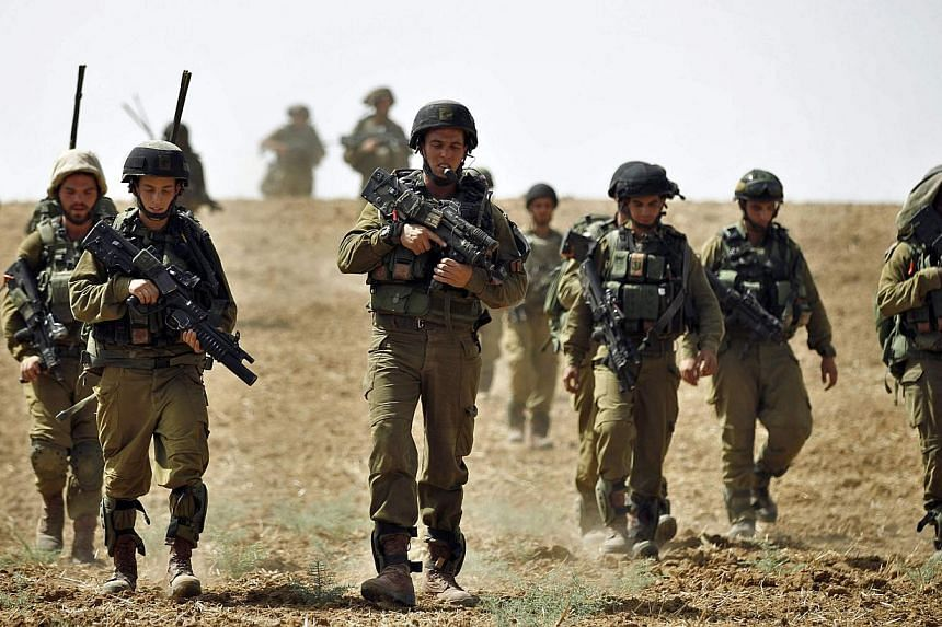 Israeli soldiers from the Nahal Infantry Brigade walk across a field near central Gaza Strip on July 12, 2014. -- PHOTO: AFP