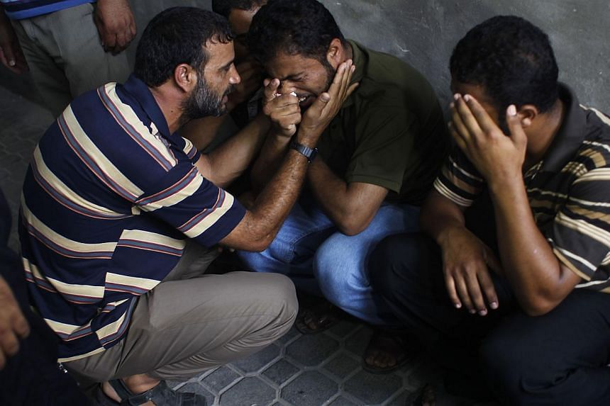 The father (centre) of three-year-old Palestinian child, Mouid al-Araj, mourns during his sons' funeral in Khan Yunis, in the southern Gaza Strip on July 13, 2014. France's foreign minister called on Sunday for an immediate ceasefire in the Gaza Stri