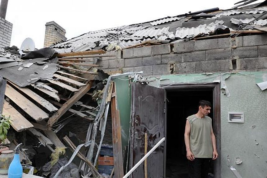 A man stands on July 13, 2014, in a house destroyed after yesterday's bombardments carried out by Ukrainian armed forces in the village of Maryinka, 20 km southwest of Donetsk.Escalating clashes between pro-Kremlin separatists and Ukrainian for