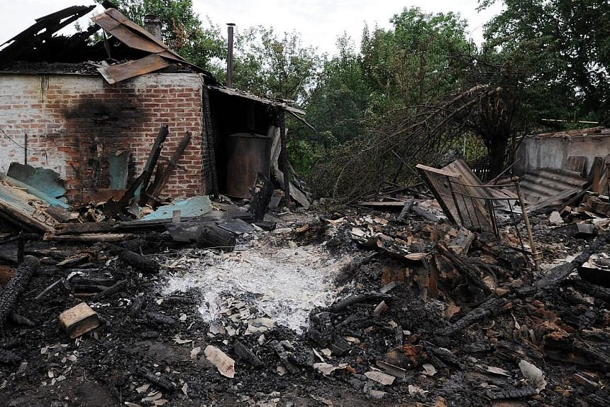 """A picture taken on July 13, 2014, shows a house destroyed after yesterday's bombardments carried out by Ukrainian armed forces in the village of Maryinka, 20 km southwest of Donetsk.Moscow on Sunday warned Kiev of """"irreversible consequences"""" af"""