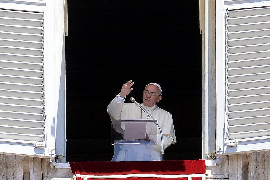 """Pope Francis waves as he addresses his Sunday Angelus from the window of his study overlooking St.Peter's Square at the Vatican on July 6, 2014.Pope Francis promised """"solutions"""" to the issue of priestly celibacy in an interview on Sunday that r"""