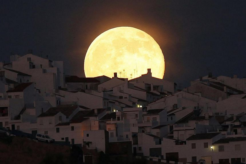 The Supermoon rises over houses in Olvera, in the southern Spanish province of Cadiz, July 12, 2014. -- PHOTO: REUTERS