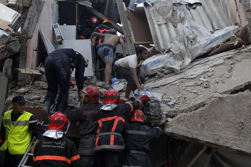 Firefighters search for victims under the rubble after buildings collapsed in downtown Casablanca on July 11, 2014. The death toll after three buildings collapsed in Morocco's largest city and commercial capital Casablanca rose to 23 on Sunday,