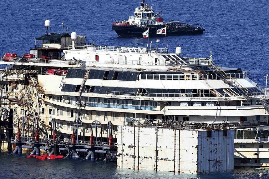 The cruise liner Costa Concordia is seen at Giglio harbour, Giglio Island on July 13, 2014.An unprecedented operation to refloat the shipwrecked Costa Concordia has begun in Italy, with salvage workers attempting to raise the rusty liner from i