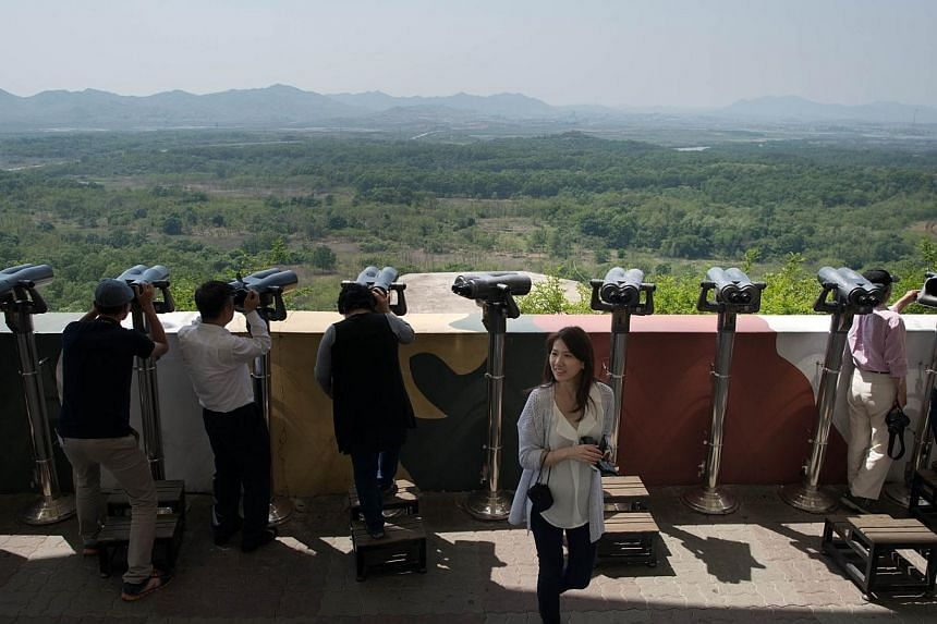 Tourists look out towards North Korea at the Dora Observatory near the truce village of Panmunjom in the Demilitarized Zone (DMZ) between North and South Korea on May 14, 2014.The two Koreas will hold talks this week to discuss logistics arising from