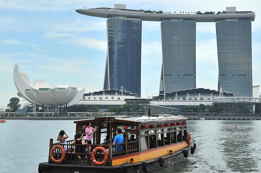 A bumboat cruising on the Singapore River with Marina Bay Sands (MBS) and the ArtScience Museum in the backgroud on 8 May 2014.About 52,000 people attended the annual STJobs Career and Development Fair organised by Singapore Press Holdings from