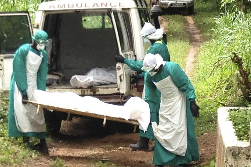 Health workers carry the body of an Ebola virus victim in Kenema, Sierra Leone, on June 25, 2014. Governments and health agencies trying to contain the world's deadliest ever Ebola epidemic in West Africa fear the contagion could be worse than r