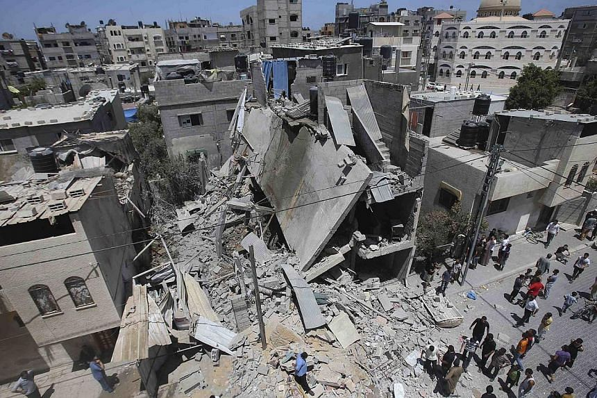 """Palestinians gather around the remains of a house, which police said was destroyed in an Israeli air strike, in Rafah in the southern Gaza Strip on July 14, 2014.The Arab League has called on the """"international community"""" to end Israeli air str"""