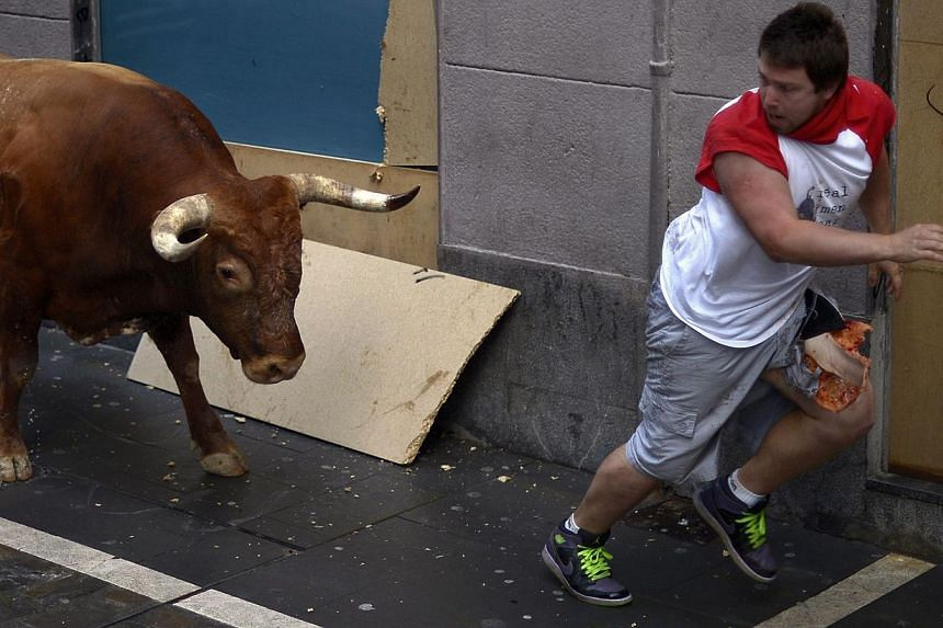 An injured runner is chased by a Miura fighting bull at Estafeta corner during the eighth running of the bulls of the San Fermin festival in Pamplona on July 14, 2014. A bull gored two men after breaking away from the pack and chasing them throu