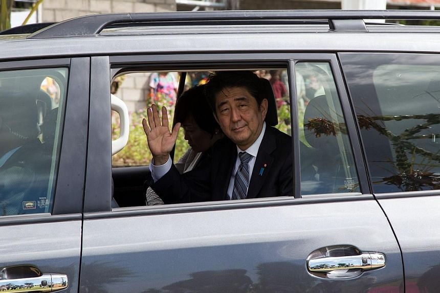 Japan's Prime Minister Shinzo Abe waves to the local during a visit to Wewak in Papua New Guinea on July 11, 2014.Japanese Prime Minister Shinzo Abe said on Monday that he wants to hold a summit meeting with China at the Apec regional leaders m