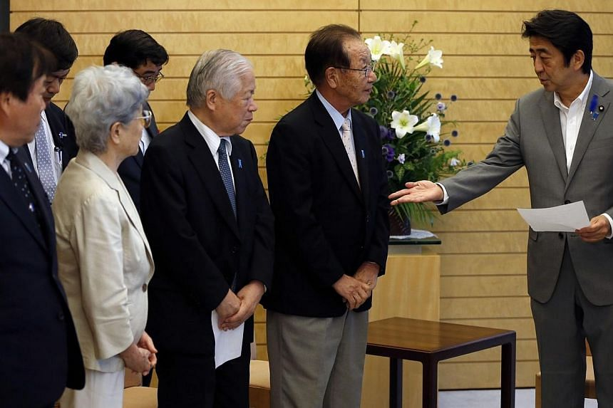 Japan's Prime Minister Shinzo Abe (right) receives a petition from members of abduction issue groups at his official residence in Tokyo on July 4, 2014.As Japan presses North Korea for information on the fate of Japanese citizens abducted decad