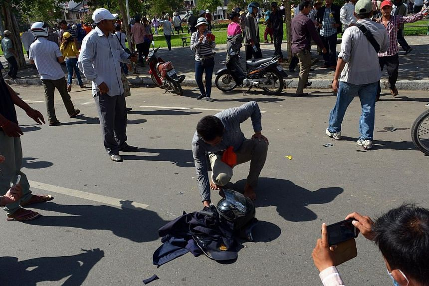 A Cambodian demonstrator prepares to burn the clothes of a security guard during a protest calling for authorities to open Freedom Park to open in Phnom Penh on July 15, 2014. -- PHOTO: AFP