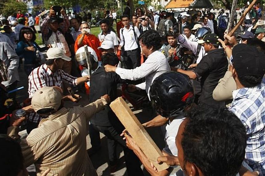 Police officers scuffle with protesters during clashes at Freedom Park in central Phnom Penh on July 15, 2014. -- PHOTO: REUTERS