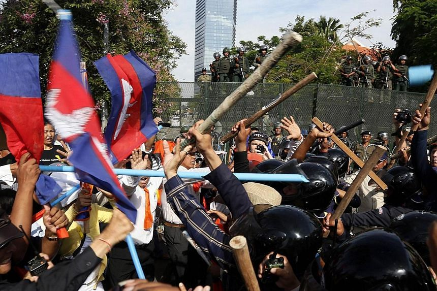 Cambodian security guards clash with demonstrators protesting for Freedom Park to open in Phnom Penh on July 15, 2014. -- PHOTO: AFP