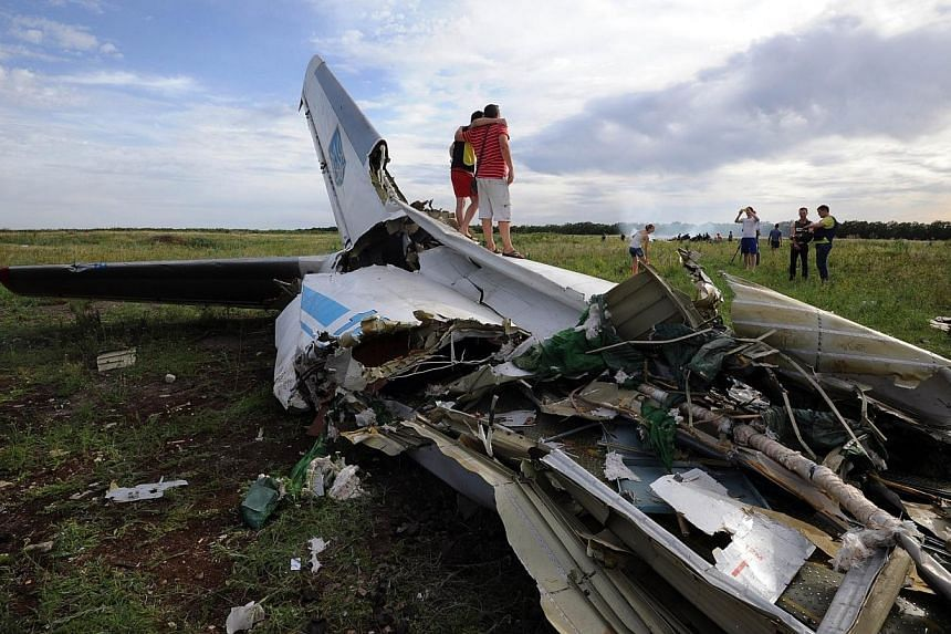 People pose on July 14, 2014 while standing on the wreckage of a Ukrainian AN-26 military transport plane after it was shot down by a missile in the village of Davydo-Mykilske, east of Lougansk near the Russian border.The Ukrainian military sai