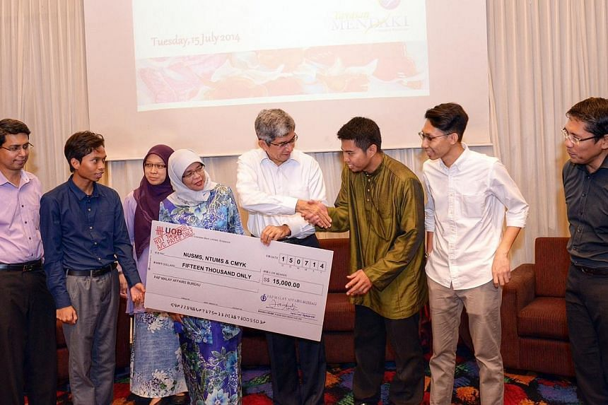 Dr Yaacob Ibrahim (centre, in white) the Minister-in-charge of Muslim Affairs, presenting a cheque for $15,000 to NTUMS president Khairul Anwar Ahmad Basha. Together with them are (from left) PAP MP Muhammad Faishal Ibrahim, NUSMS president Muhammad