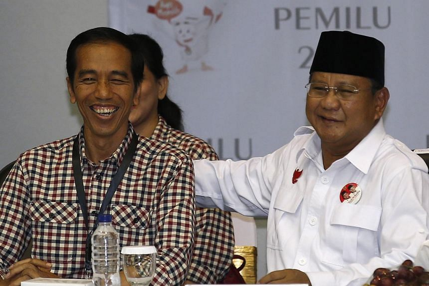 """Indonesian presidential candidates Prabowo Subianto (right) and Joko """"Jokowi"""" Widodo attending a ceremony to draw ballot numbers at the Election Commission in Jakarta on June 1, 2014. -- PHOTO: REUTERS"""